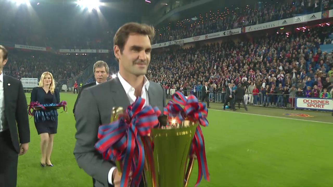 Roger Federer übergibt den Meisterpokal